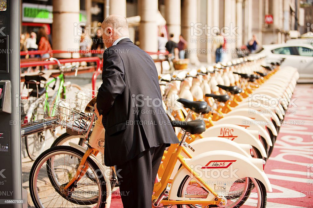 Man in business wear renting a bike, Milan, Italy royalty-free stock photo