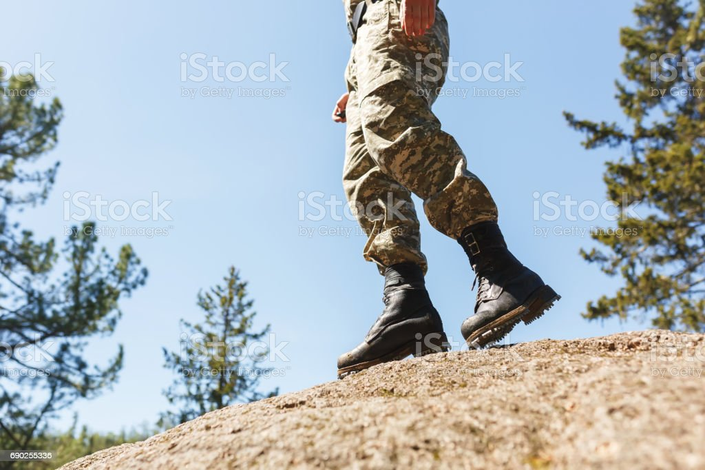 A man in camouflage old shoes with spikes for climbing on rocks. Trikoni. Tricouni stock photo