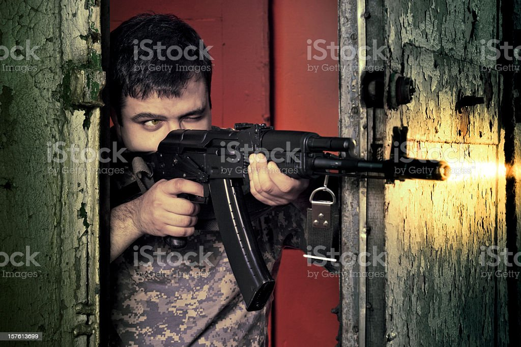 Man in camouflage shooting with assault rifle AK-47 royalty-free stock photo