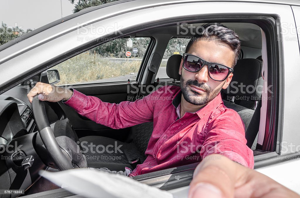 man in car pay road tax stock photo