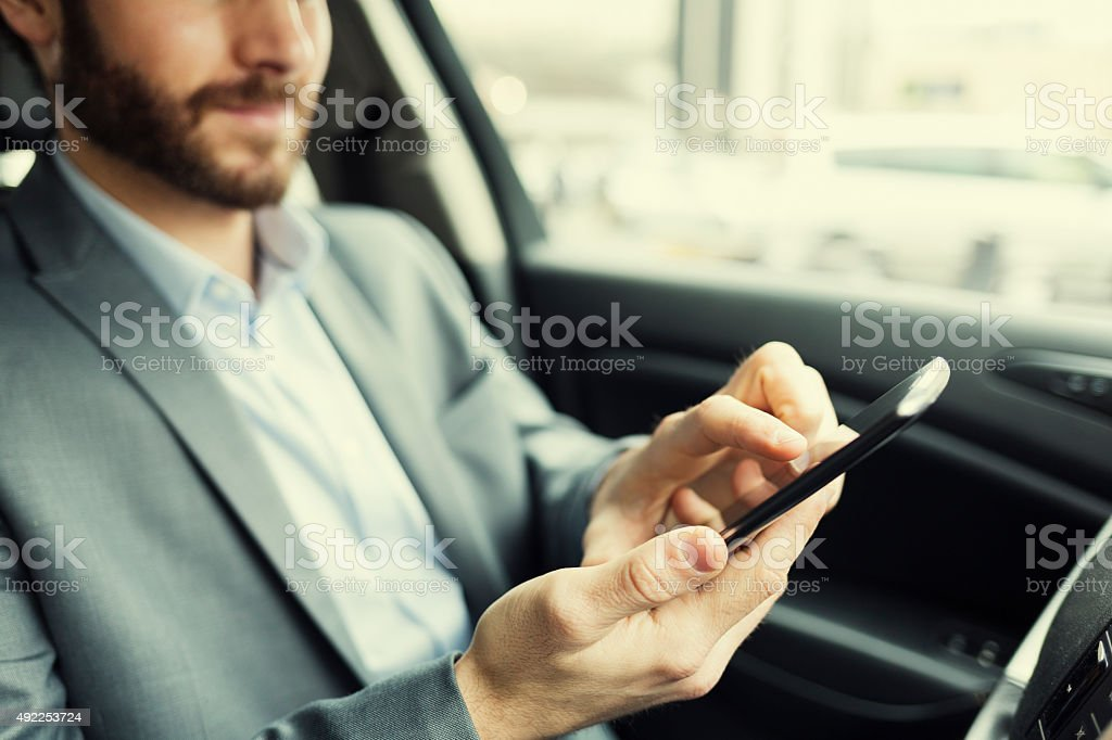 Man in car typing text message on mobile phone stock photo