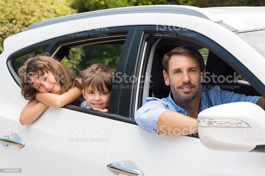 Man in car with children stock photo