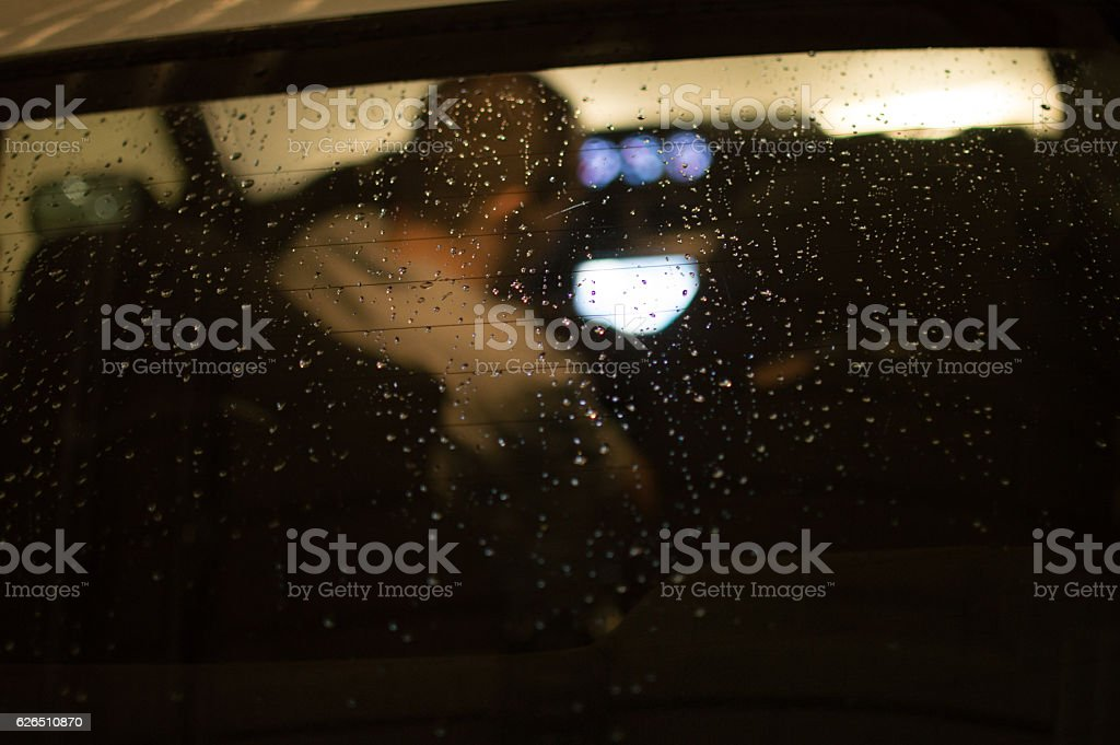 Man in car with raindrops stock photo