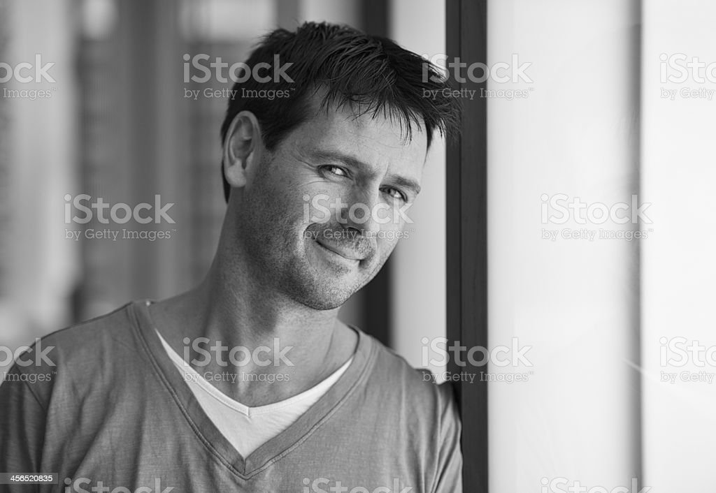 A man in casual wear smiles in this black-and-white photo. royalty-free stock photo