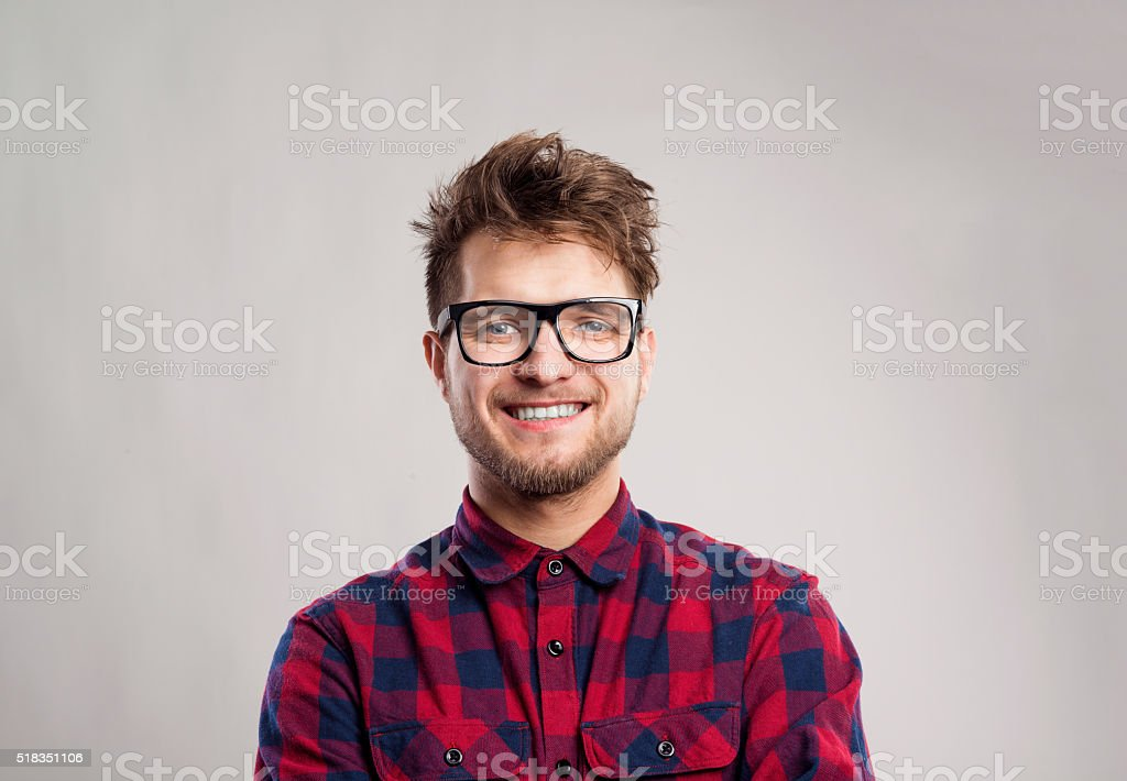 Man in checked shirt and eyeglasses against gray background. stock photo