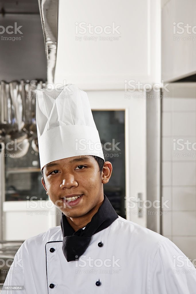 man in chef uniform posing in kitchen stock photo