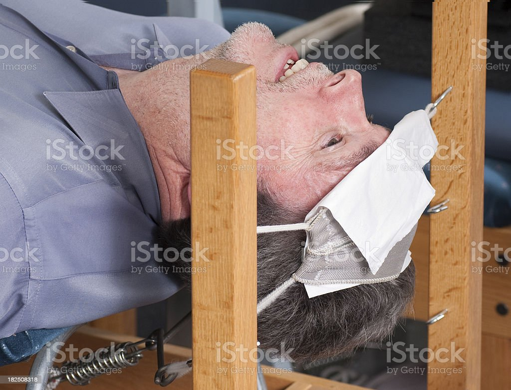 man in chiropractic traction device stock photo