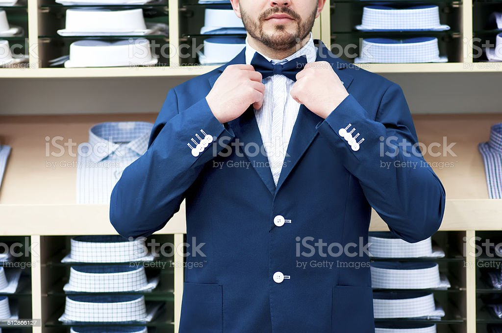 Man in classic suit against showcase with shirts stock photo