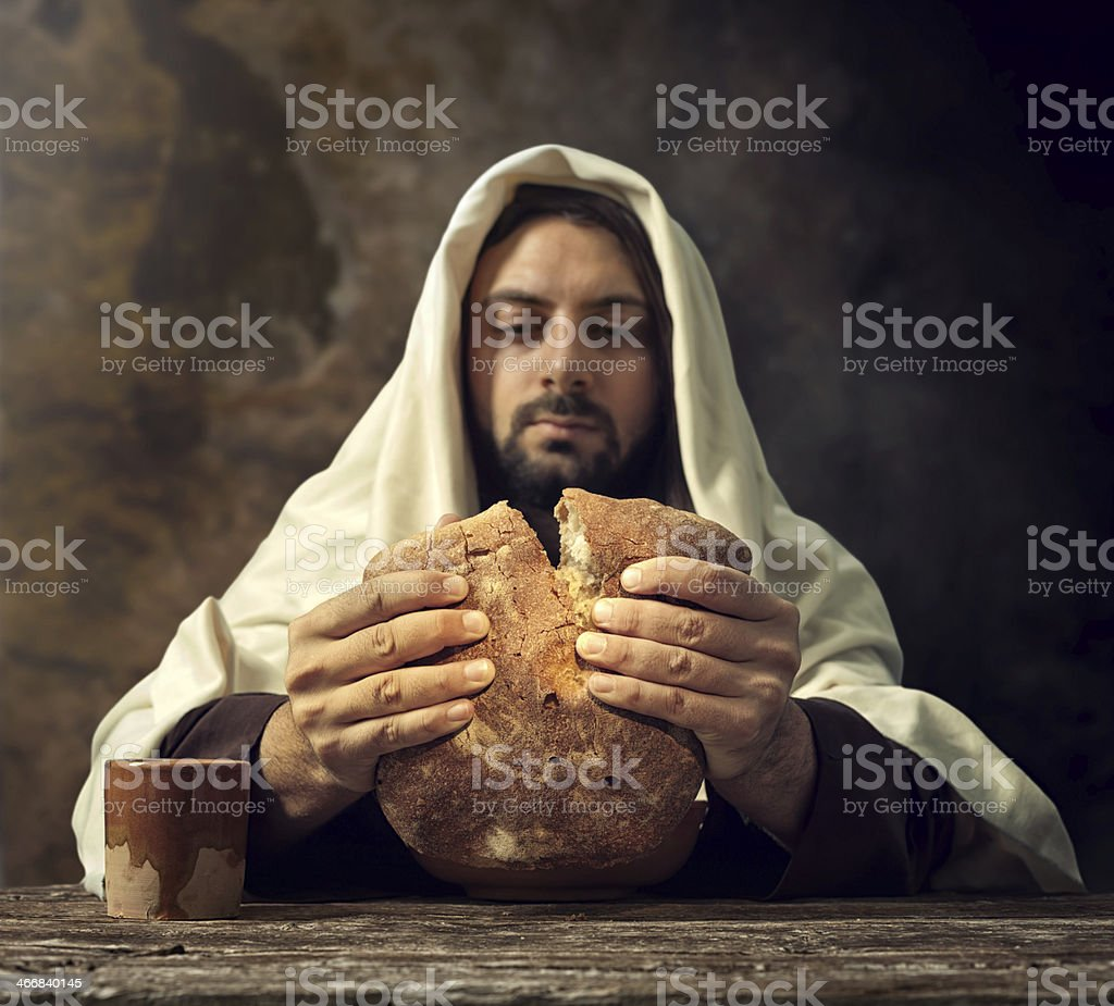 Man in cloak tearing bread into two  stock photo