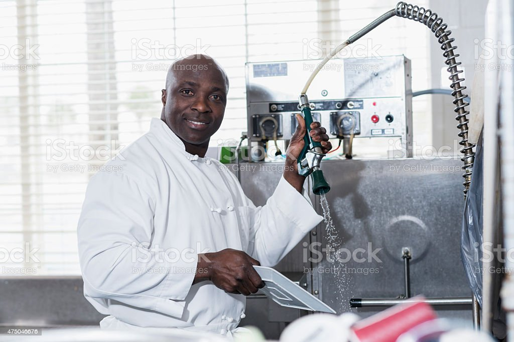 Man in commercial kitchen at sink cleaning dishes stock photo