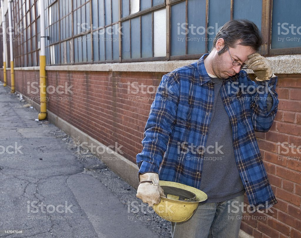 Man in construction gear leaning against a brick building stock photo
