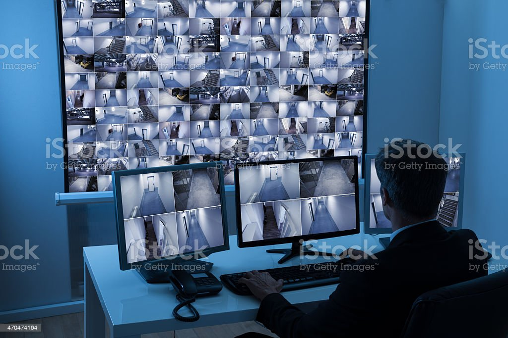 Man In Control Room Monitoring Cctv Footage stock photo