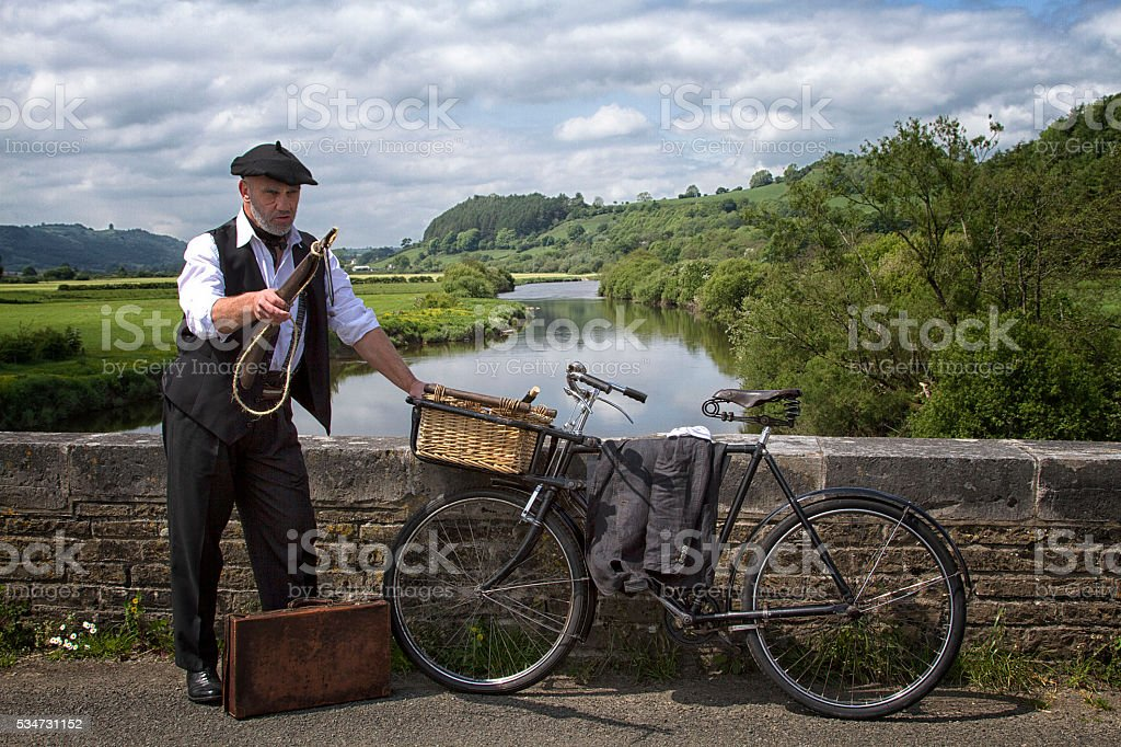 Man in costume by a river with a bicycle stock photo