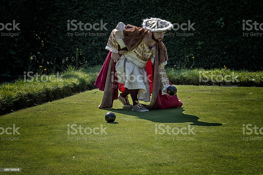Man in costume playing bowls stock photo