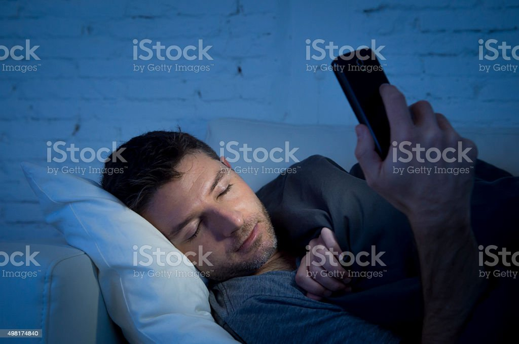 man in couch falling asleep using mobile phone stock photo