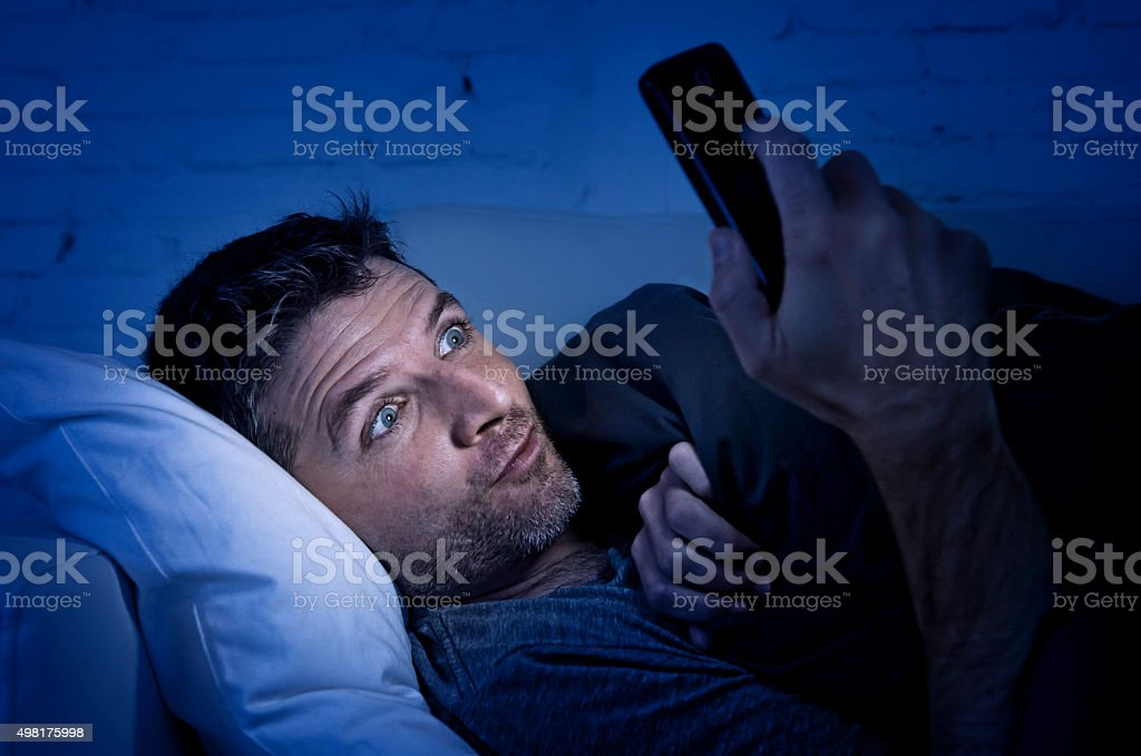 man in couch using mobile phone watching online porn stock photo