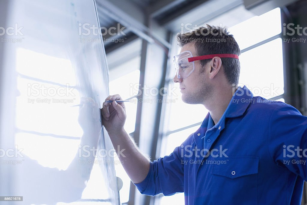Man in coveralls writing on whiteboard royalty-free stock photo