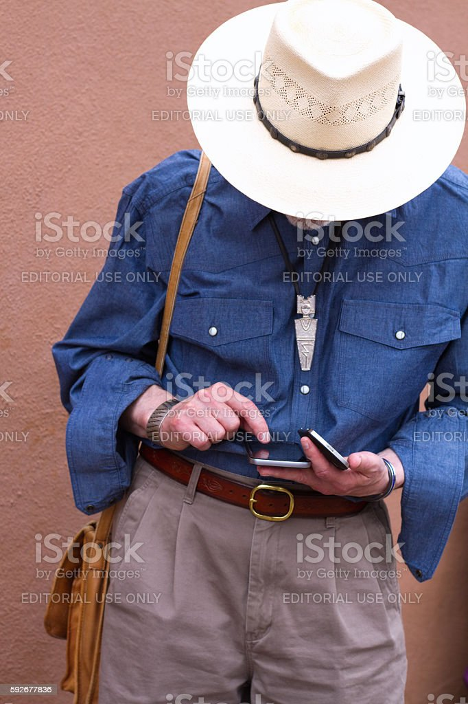 Man in Cowboy Hat Looking Down at Two Smartphones stock photo