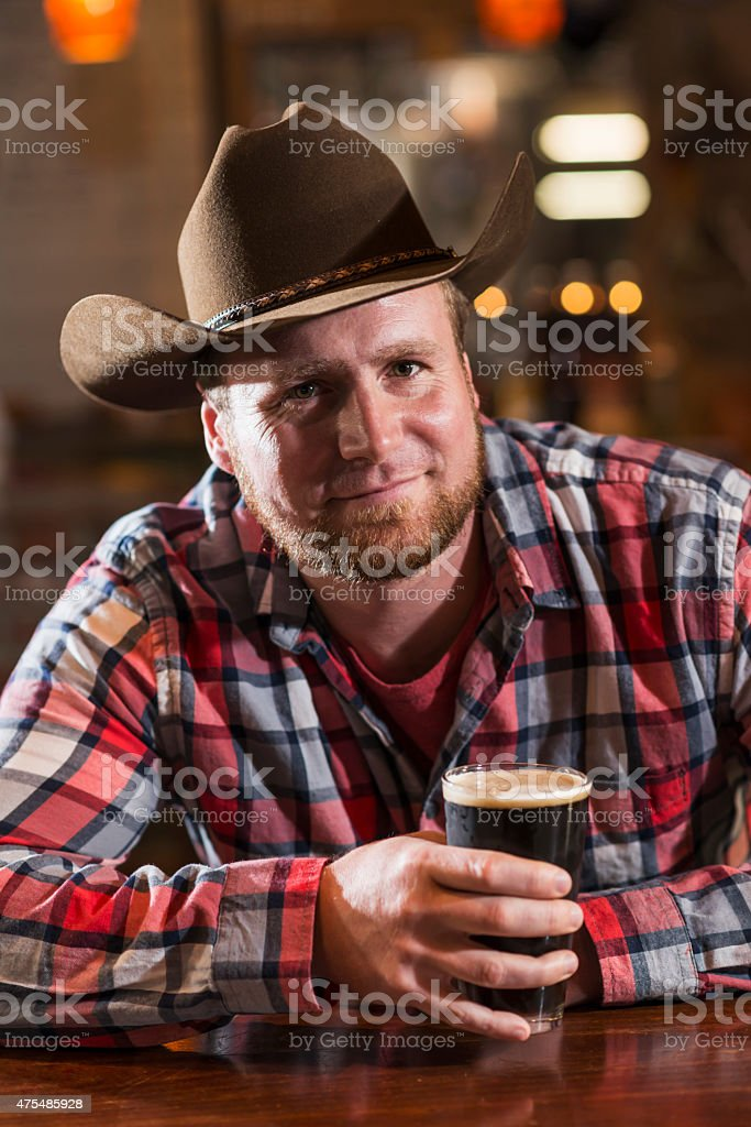 Man in cowboy hat sitting at bar table drinking beer stock photo
