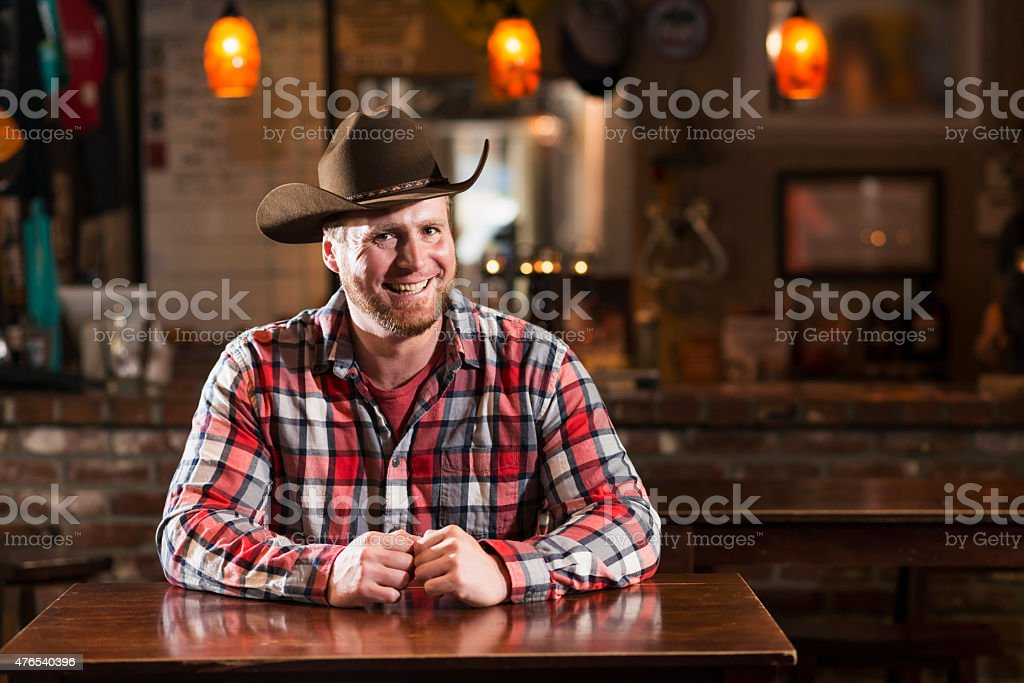 Man in cowboy hat sitting at table in bar stock photo