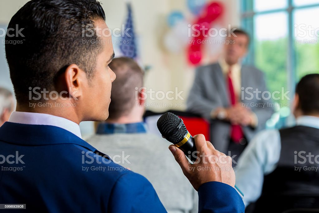 Man in crowd asking question during town hall meeting stock photo