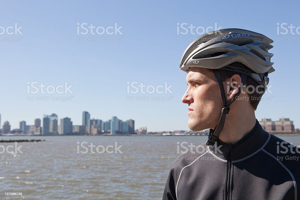 Man in cycling gear looking at view stock photo
