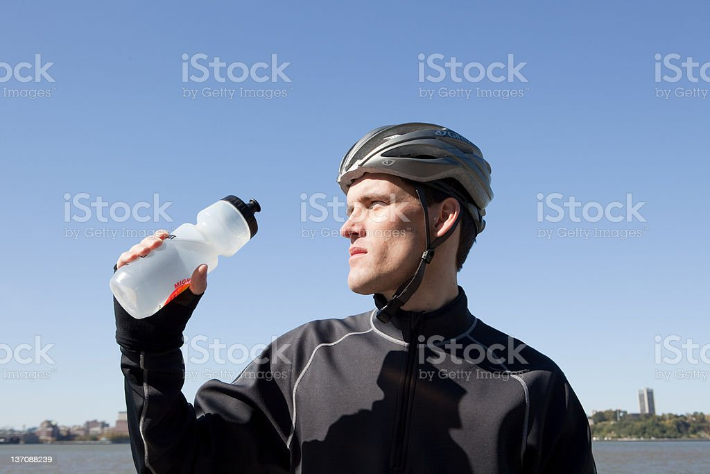 Man in cycling gear quenching thirst stock photo