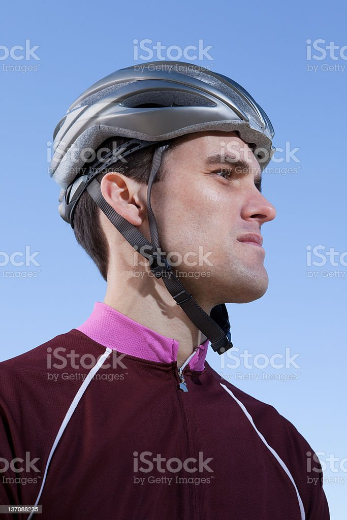 Man in cycling helmet looking into distance stock photo