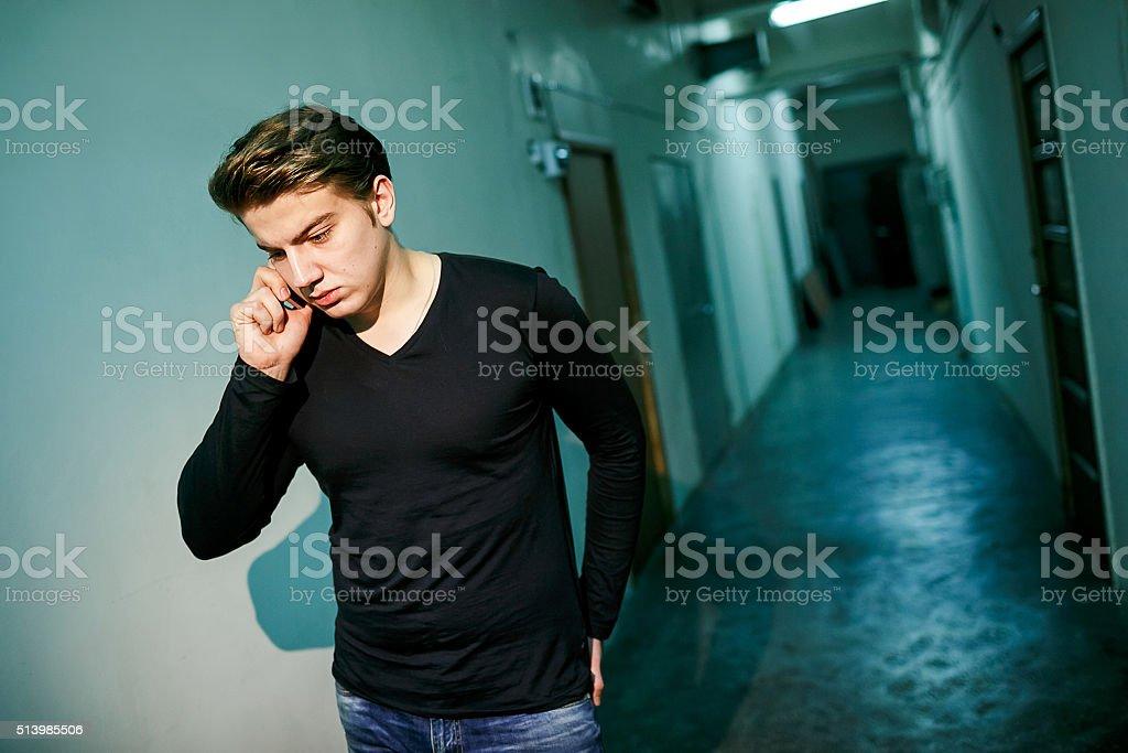 Man in dark corridor with backlight talking on phone, walked stock photo