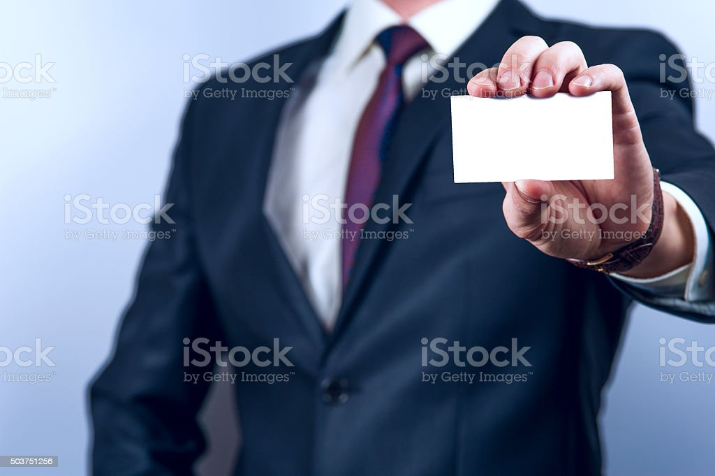 Man in dark suit holds business card stock photo