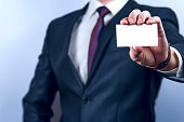 Man in dark suit holds business card