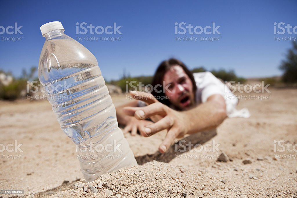 Man in Desert Reaching for Water stock photo