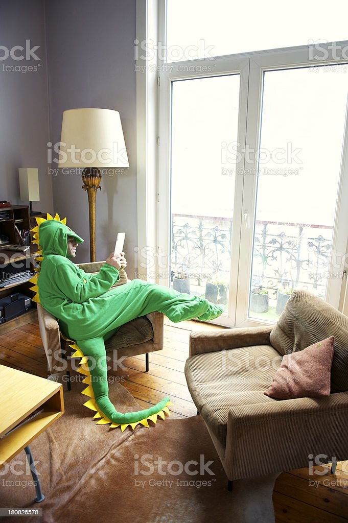 Man in Dinosaur Suit Relaxes Home Using Digital Tablet Computer stock photo