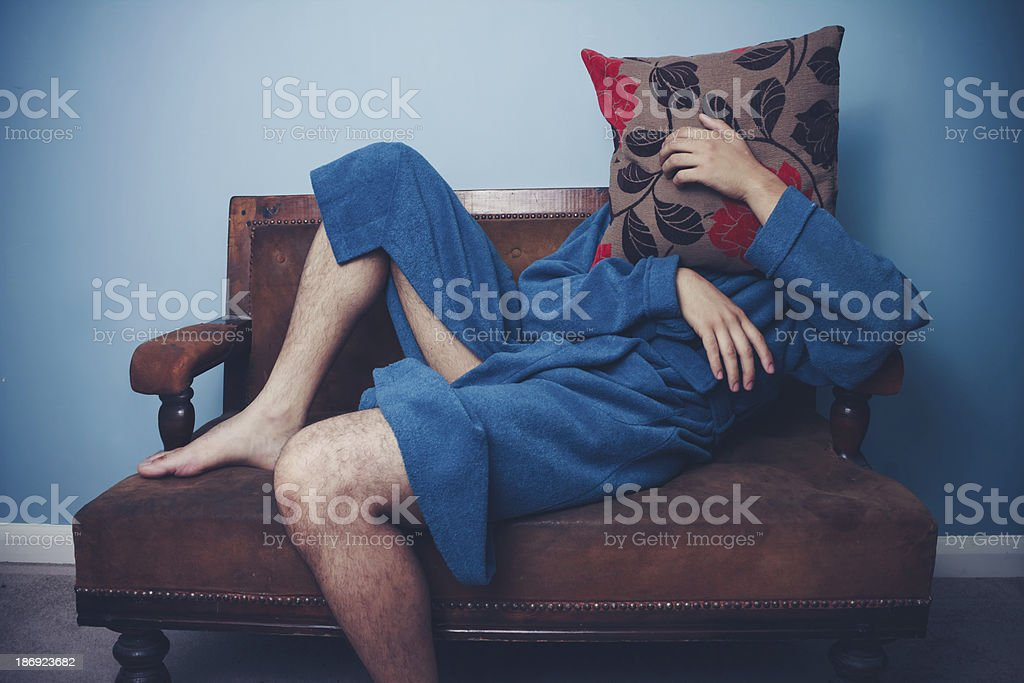 Man in dressing gown hiding behind cushion royalty-free stock photo