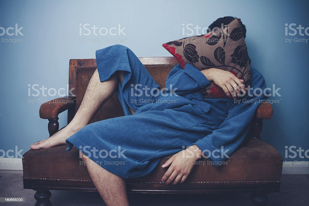 Man in dressing gown sleeping with face behind cushion royalty-free stock photo