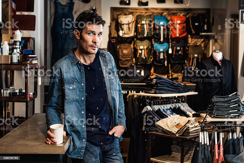 Man in drinking coffee inside a fashion store.