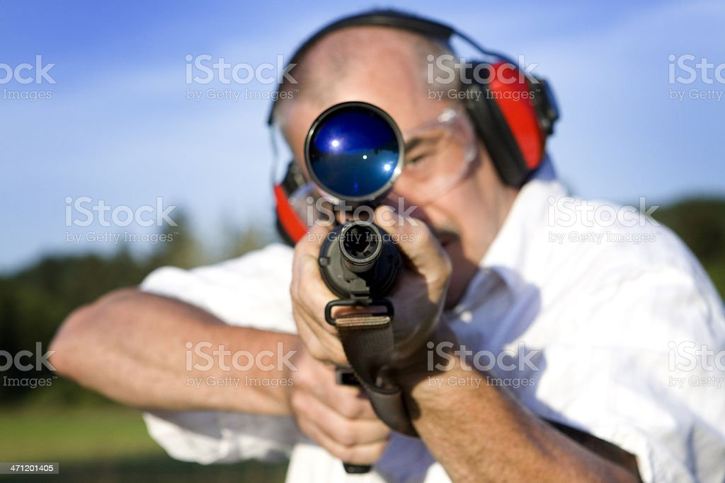 Man in ear coverings and goggles is target shooting. stock photo