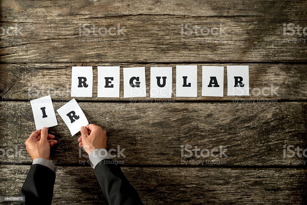 Man in elegant suit removing letters IR from word irregular stock photo