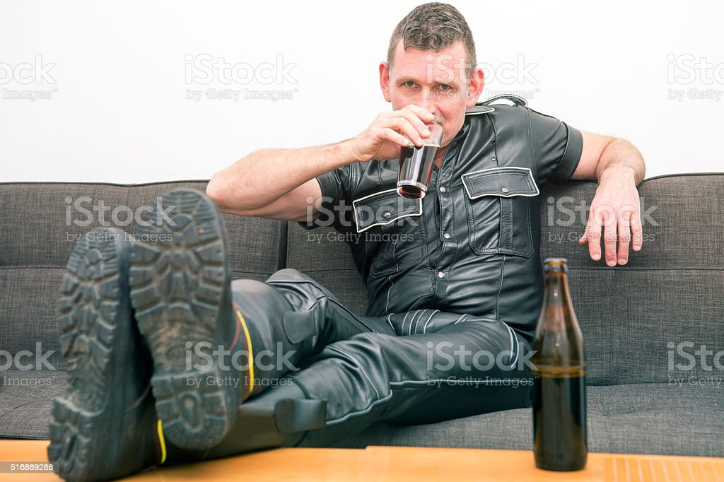 man in fetish leather gear sitting on couch stock photo