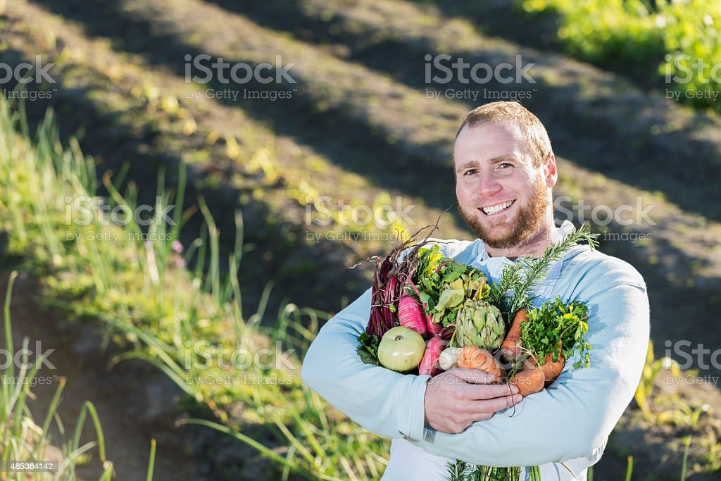 Man in field with bountiful harvest of vegetables stock photo