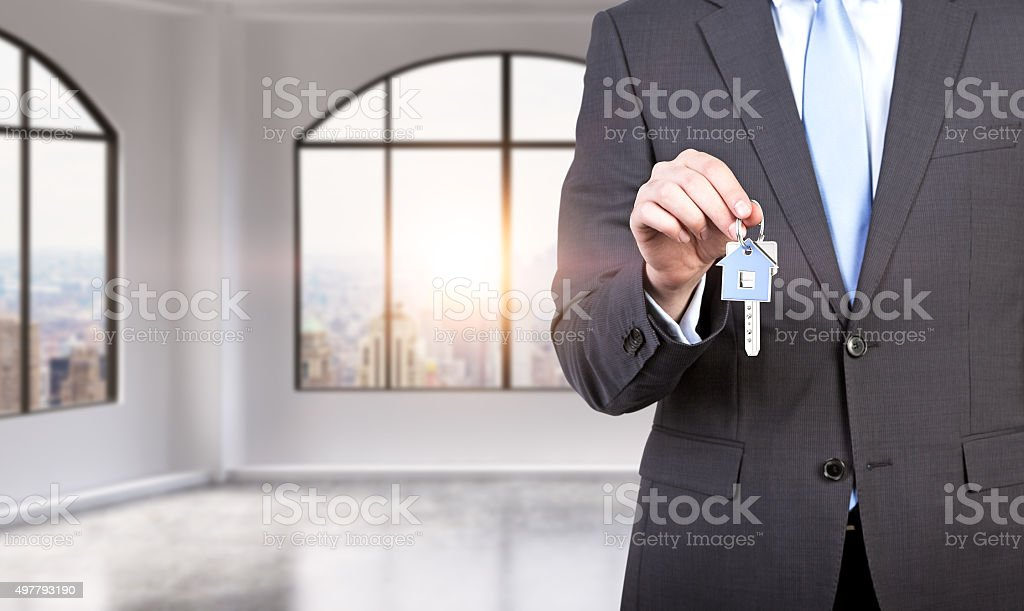 man in formal suit holds a key stock photo