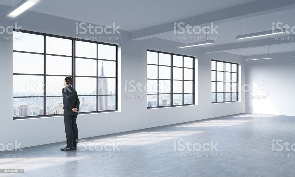 man in formal suit who is looking out the window stock photo