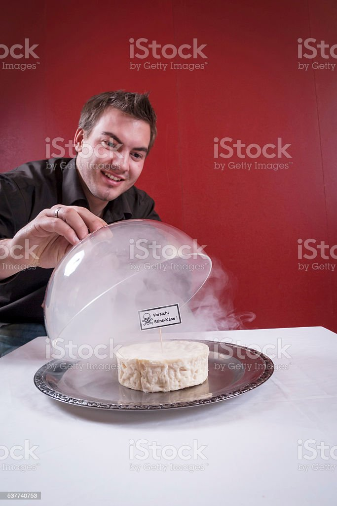 Man in front of a plate with cheese and cover stock photo