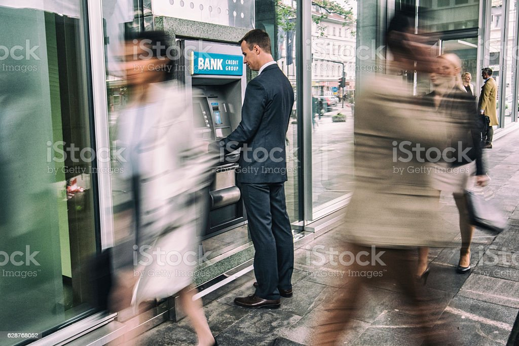 Man in front of an ATM machine stock photo