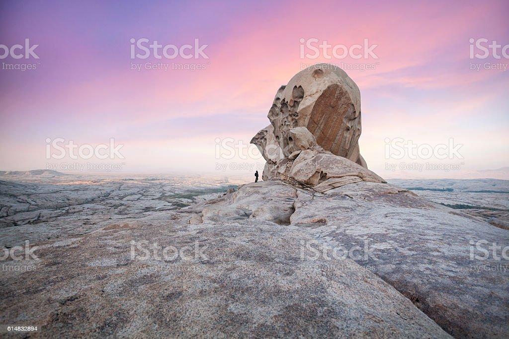 Man in front of big rock in stone desert stock photo