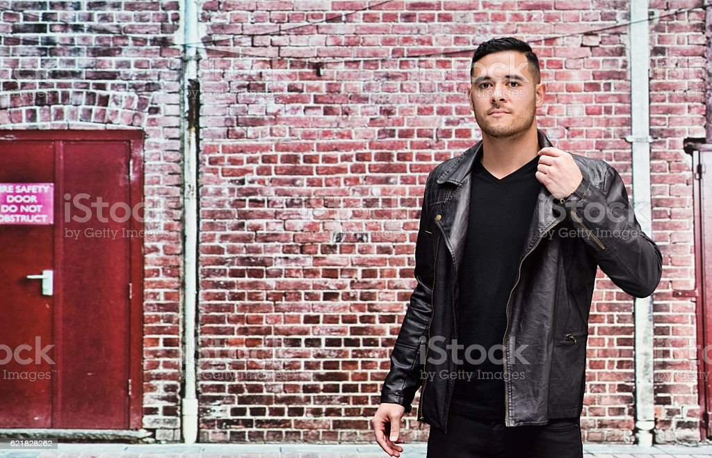 Man in front of brick wall outdoors stock photo
