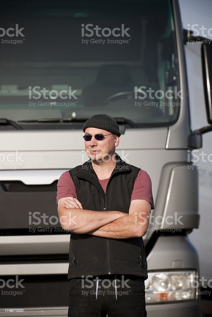 \'Middle aged man, 47 years old. Focus is on man, truck in...