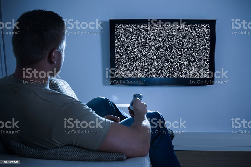Man In Front Of Television With No Signal stock photo