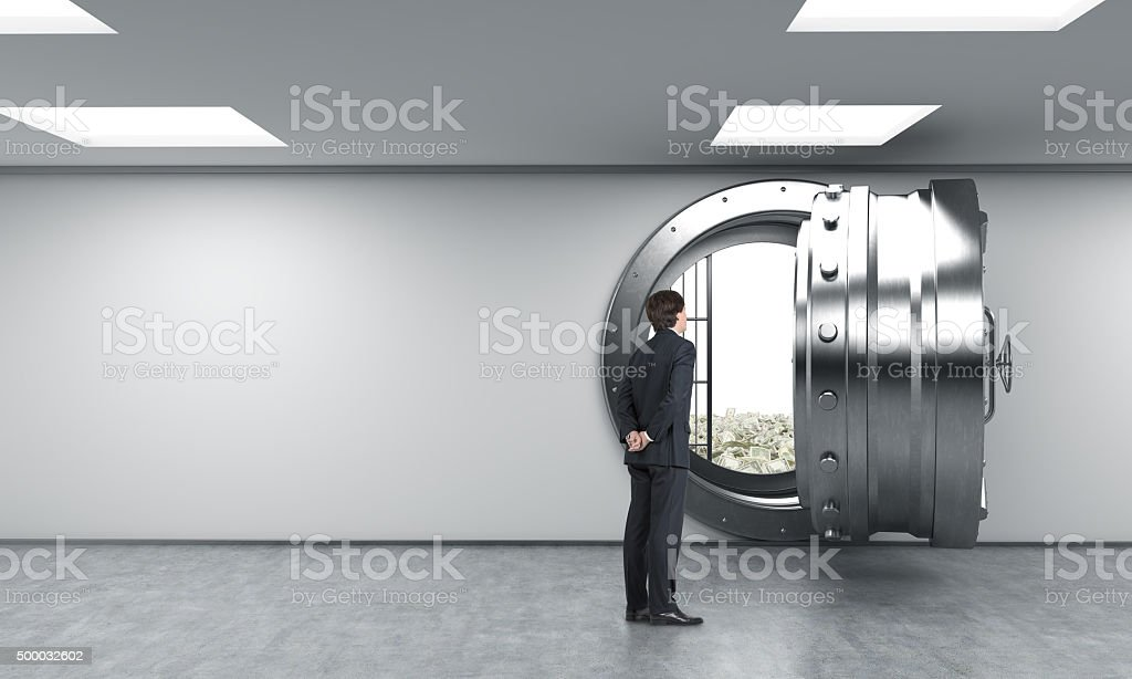 man in front of unlocked safe in bank, dollars inside stock photo