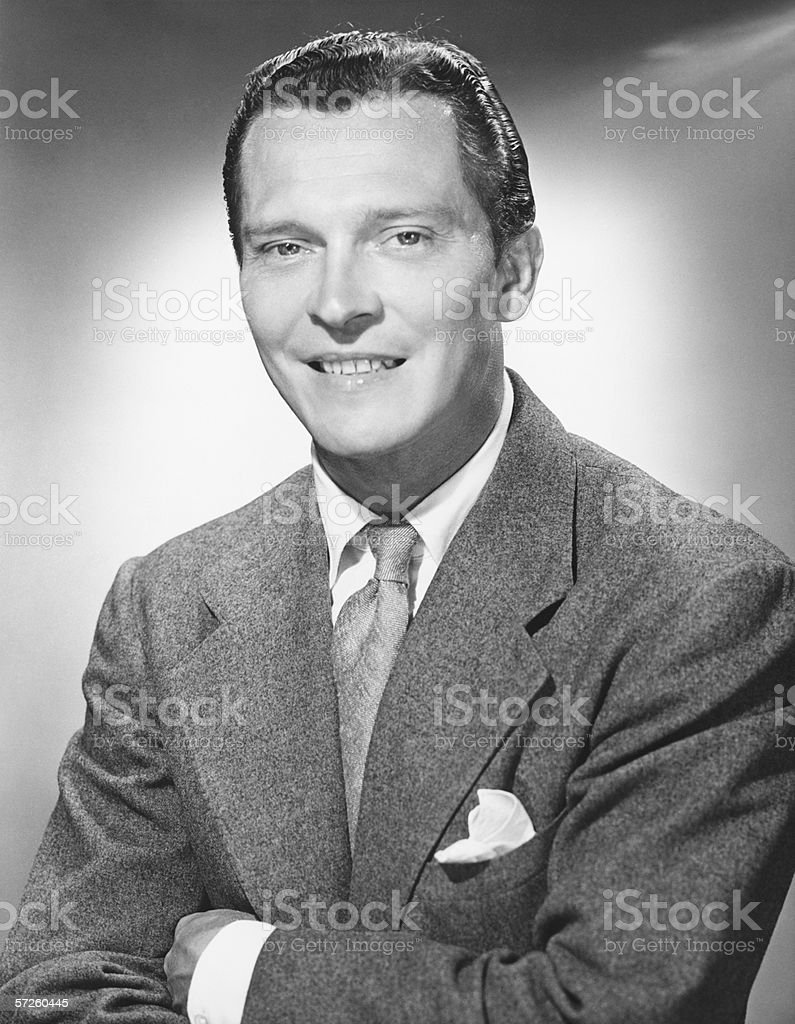 Man in full suit posing in studio, (B&W), close-up, portrait stock photo